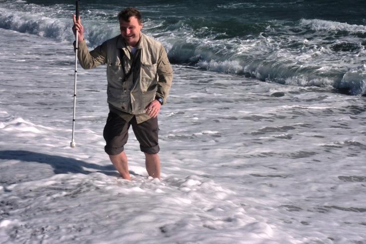 Per, stehend im Ozean, Blindenstock in der Hand, hochgekrempelte Hose.