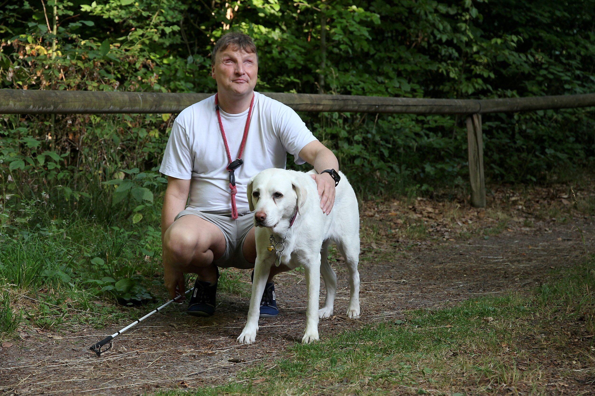 """Im Wald. Per kniet neben seinem Hund Peggy. Foto von HNA-Artikel """"Blinder Waldläufer, seit neun Jahren ungeküsst"""", Sommer 2018"""